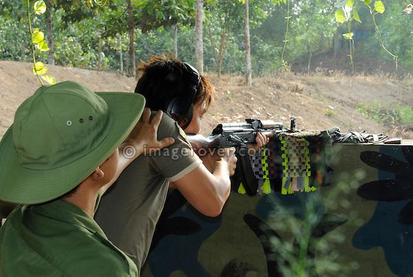 Asia, Vietnam, Cu Chi nr. Ho Chi Minh City (Saigon). Cu Chi Tunnels. Tourist enjoying himself at a shooting gallery.