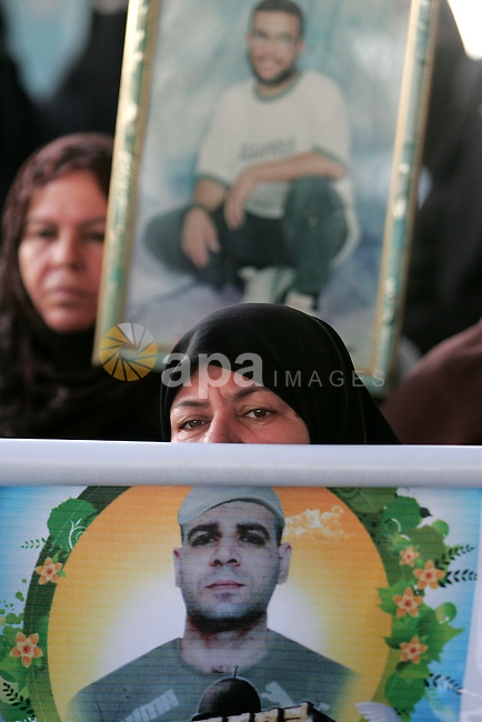 A Palestinian woman hold a picture of jailed relatives during a protest calling for the release of Palestinian prisoners from Israeli jails in southern Gaza Strip town of Khan Younis on November 1,2010 . Photo By Khaled Khaled