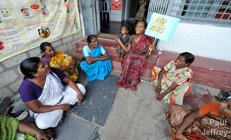 K Lakshmi (holding the sign), a woman living with HIV, discusses how to combat stigma and discrimination with other women in the Lutheran Counseling and Health Care Center in Chilakaluripet, a town in Andhra Pradesh, India. Her daughter is beside her. (Note Special Instructions below.)