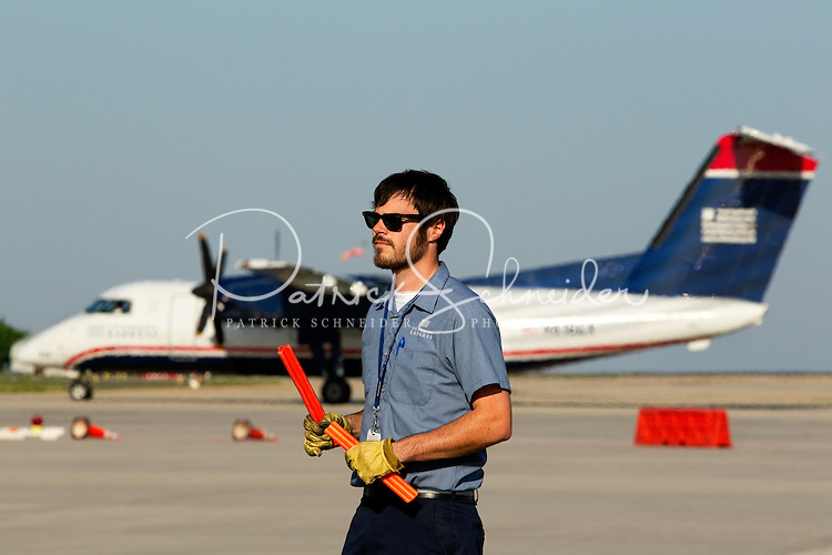 A US Airways employee signals in planes at Charlotte-Douglas International Airport in Charlotte, North Carolina. The downtown Charlotte skyline is in the background. Charlotte-based photographer has other images of transportation, airplanes on runways (and taking off and landing) and interior/exterior airport images of Charlotte-Douglas Intl Airport in portfolio.