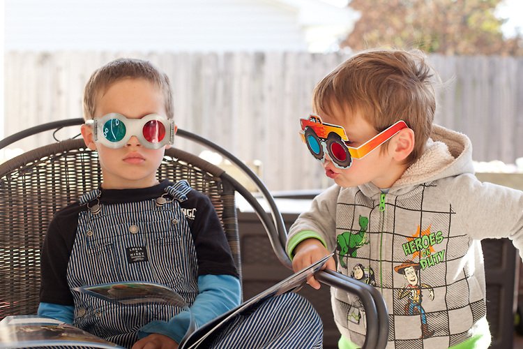 My sons, age six, left, and age three, right, read 3-D books in our backyard.
