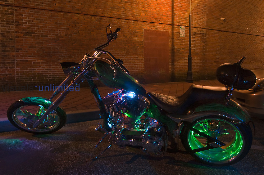 Harley Davidson motorcycle parked on a street at night and illuminated by multicolored overhead lights.