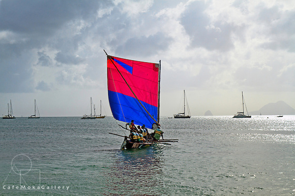 A yole (traditional sailing boat) with red and blue sail sailing with crew - St Anne, Martinique