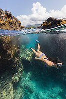 A woman snorkels in clear water off the Kona coast of the Big Island.