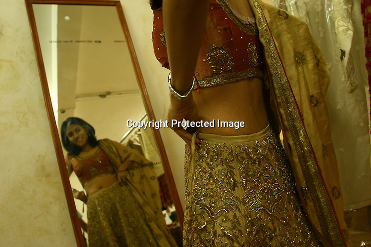 An Indian woman (soon to be bride) tries her wedding outfit  at a designer store in New Delhi, India. Photo: Sanjit Das/Panos