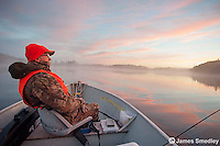 Moose hunter sitting in his boat on a calm lake.