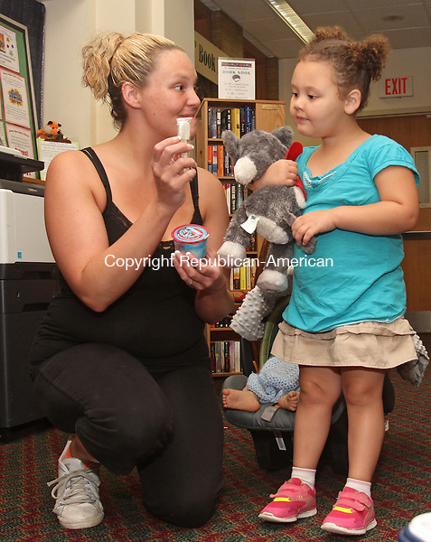 Winsted, CT-071815MK10 Chelsey Andrews and Ellie, her daughter, get ready to enjoy a frozen treat at the Beardsley and Memorial Library in Winsted Saturday afternoon.  Linda Gordon, program coordinator, said there was a selection of 100 items of ice cream, popsicles or frozen ices for children as well as adults to choose from.  The activity was held to celebrate national ice cream day, which is today, with those patrons who borrowed books or participated in the library's presentations.   Michael Kabelka / Republican-American