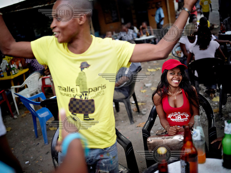 A young man dances at an outdoor bar in Kinshasa. The middle classes almost don't exist in D.R. Congo; the more wealthy youngsters have relatives living in Europe.
