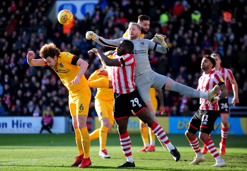 Northampton Town's David Cornell punches clear under pressure from Lincoln City's John Akinde, and over Ash Taylor<br /> <br /> Photographer Andrew Vaughan/CameraSport<br /> <br /> The EFL Sky Bet League Two - Lincoln City v Northampton Town - Saturday 9th February 2019 - Sincil Bank - Lincoln<br /> <br /> World Copyright © 2019 CameraSport. All rights reserved. 43 Linden Ave. Countesthorpe. Leicester. England. LE8 5PG - Tel: +44 (0) 116 277 4147 - admin@camerasport.com - www.camerasport.com