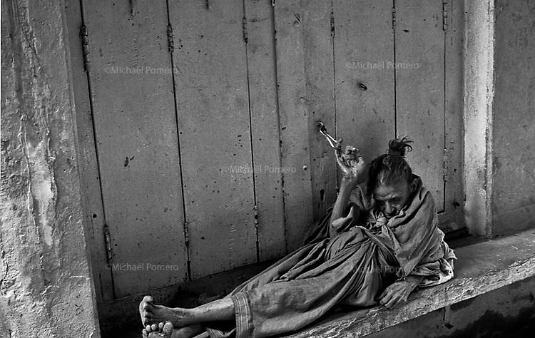 Varanasi (Uttar Pradesh)<br /> <br /> Old woman sleeping in the street holding a small shop chain.<br /> <br /> Vieille femme en train de dormir dans la rue en tenant la chaine d'un petit magasin.