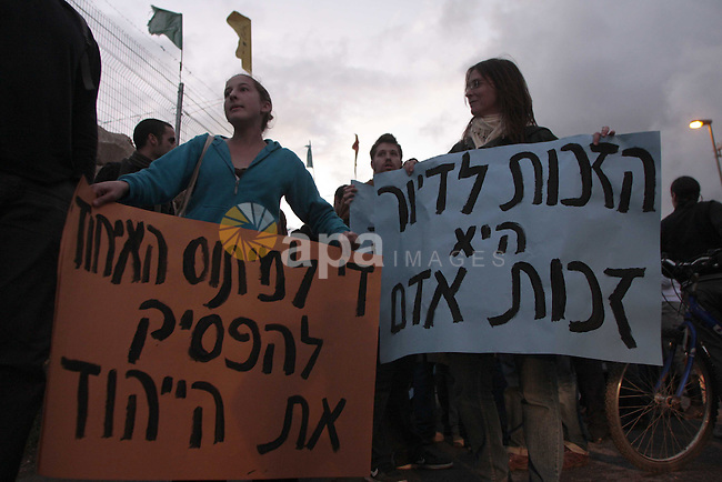 Palestinian arab residents of east Jerusalem, Israelis and foreign peace activists hold banners during a protest in the east Jerusalem neighborhood of Sheikh Jarrah, November 13, 2009. Photo by Mohamar Awad