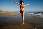 Happy girl jumps on a  beach in California, USA at sunset, dusk, CA, America