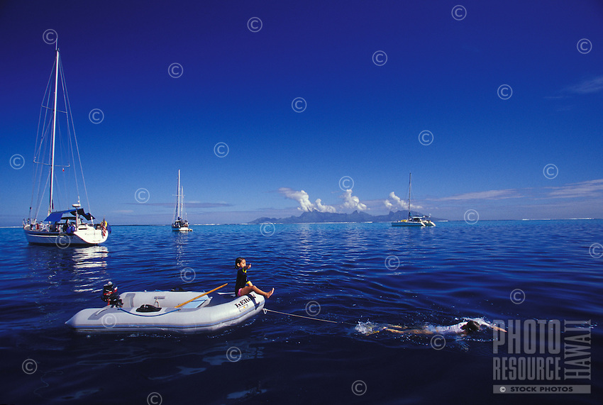 Mother swimming and  towing daughter in dinghy while at anchor in lagoon off Tahiti's Punauia district, Moorea in background