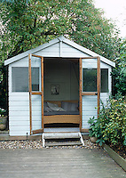 A grey-painted timber shed at the end of a small garden that has been laid with wooden decking