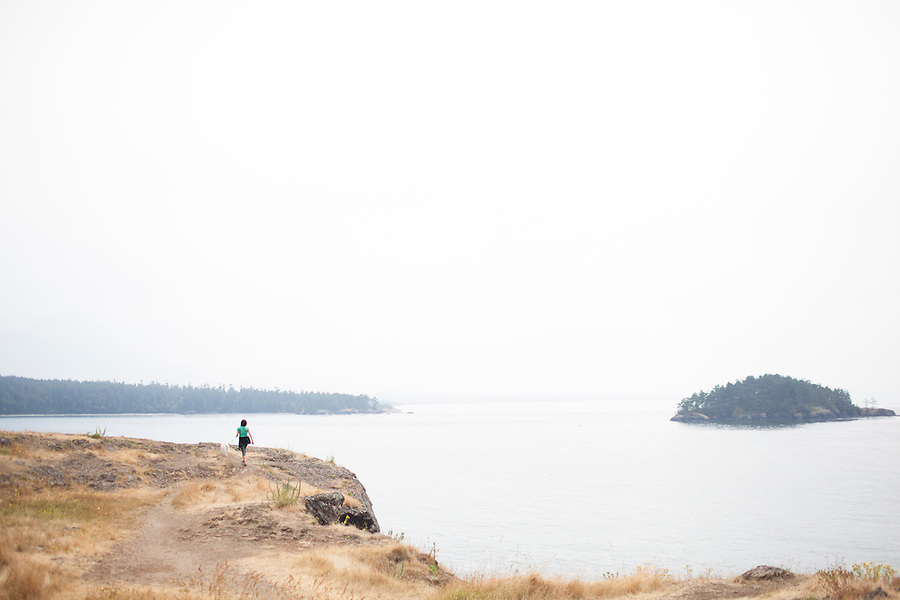 A woman walks a dog along a cliff at Deception Pass State Park, WA, USA.