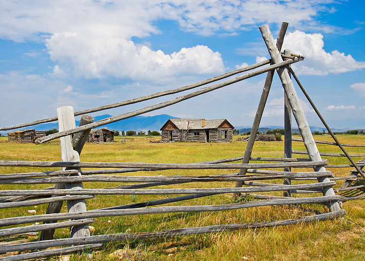 Looking through an old fence to an old homestead with back drop of blue sky and billowy white clouds.