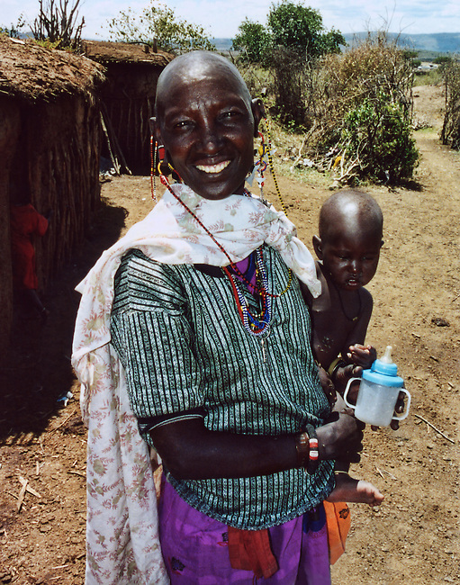 A traditionally dressed and ornamented Masai woman holding her nude baby and a sippy cup stand in front of typical wood and straw huts in her tribal location in the Masai Mara.