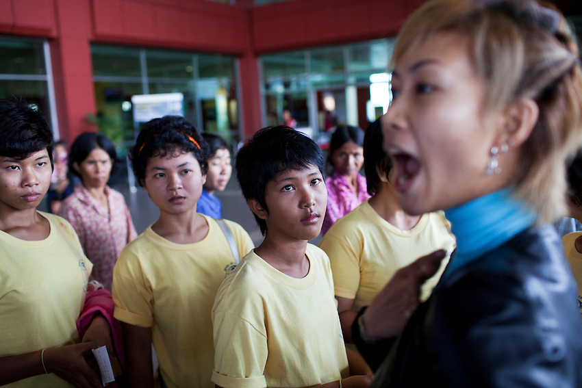 Young Cambodian maids from the Top Manpower recruitment agency watch as an employee of the company shouts obsceneties at journalists for taking photos of the group at Phnom Penh International Airport, Phnom Penh, Cambodia, October 17, 2011. The group of maids later left the country on an AirAsia flight bound for Kuala Lumpur.