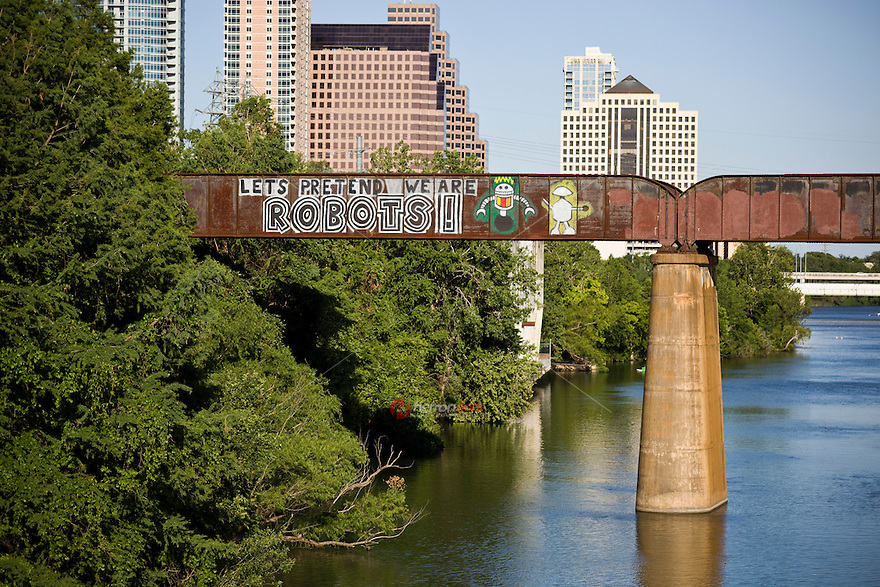 "The most famous street art in Austin is on a bridge over Lady Bird Lake, the ""Let's Pretend We Are Robots"" graffiti mural painting on the Austin Railroad Bridge over Lady Bird Lake."