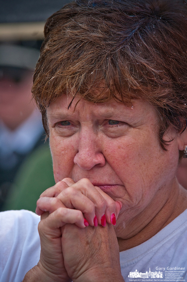 A woman holds her clasped hands as she listens to ceremonies in the rain at First Responders Park in Westerville, OH, during ceremonies marking the 10th anniversary of the attack on the World Trade Center