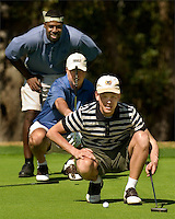 Three golfers line up a putt on the green in Amelia Island, FL