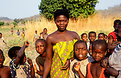 Kalepo, Tanzania. Tribal woman with brightly coloured cotton wrap dress surrounded by children.