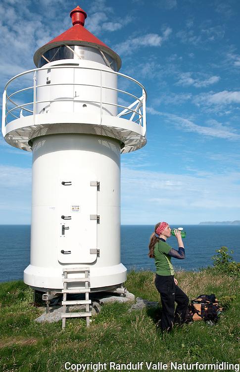 Dame ved fyrlykta på Tarhalsen på Sørøya. ---- Woman by the lighthouse at Tarhalsen, Sørøya.