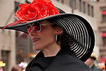 A woman wears a large black hat with red flowers to the Easter Day Parade in New York City on Fifth Avenue