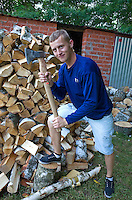 Polish teen wood chopper holding ax beside large pile of split wood. Zawady Central Poland
