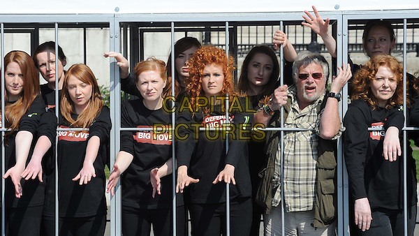 BILL ODDIE.The Big Move - photocall. Trafalgar Square, London, England. Bill Oddie Wildlife expert poses alongside a group of red-headed women who are 'crammed' into human-sized battery cages to raise awareness about the upcoming ban on barren battery-caged hens. Organised by Compassion In World Farming, who are campaigning against a delay on the ban proposed by Poland. .demonstration protest half length vest green khaki sunglasses shades check shirt cage bars black arms hands goatee facial hair.CAP/WIZ.© Wizard/Capital Pictures.