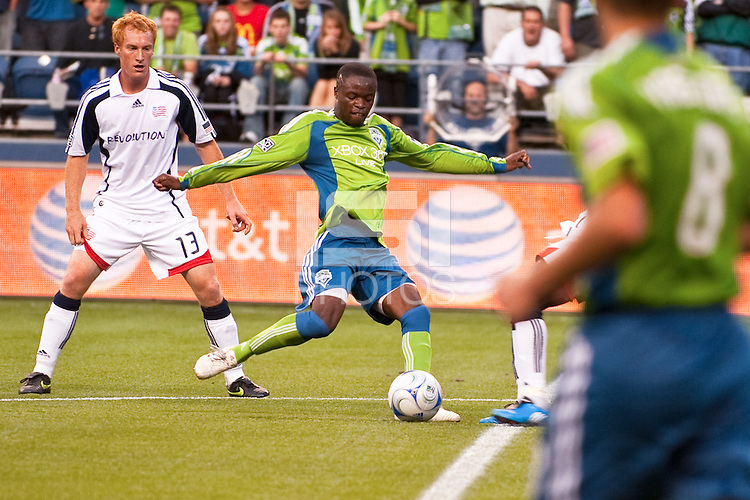 Steve Zakuani (c) of the Seattle Sounders shoots  as  Jeff Larentowicz (13) of the New England Revolution looks on in the match at the XBox Pitch at Quest Field on August 20, 2009. The Revolution defeated the Sounders 1-0.
