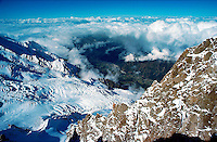 .Looking down the Bossons Glacier from the summit of the Aiguille du Midi, French Alps. A gap in the early-morning cloud shows the Chamonix valley far below...