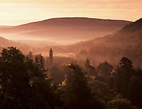 Ireland, County Wicklow, Glendalough: Wicklow mountains and Round Tower in monastic site founded in 6th century by St. Kevin through morning mist | Irland, County Wicklow, Glendalough: Morgenstimmung in den Wicklow mountains, im Morgennebel erkennt man eine Klosteranlage mit Rundturm, die im 6. Jahrhundert von St. Kevin gegruendet wurde