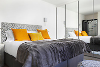 Orange cushions bring a bold injection of colour into the grey palette of this bedroom