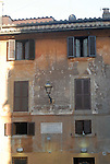 Exterior wall with window shutters on the Piazza Trilussa in the Trastevere district of Rome.