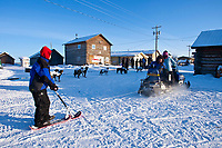 Kids of Kaltag run a snowmachine pulling a kick-sled at the checkpoint as Sonny Lindner and Ken Anderson check-in during the 2010 Iditarod
