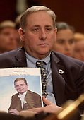 Washington, D.C. - March 23, 2004 -- Bruce DeCell of Staten Island, New York, holds a photo of his son-in-law, Mark Petrocelli, who was on the 92nd floor of Tower 1 of the World Trade Center on Septrember 11, 2001, watches testimony before the National Commission on Terrorist Attacks Upon the United States (9/11 Commission) during its 8th Public Hearing in Washington, D.C. on March 23, 2004.<br /> Credit: Ron Sachs / CNP<br /> [RESTRICTION: No New York Metro or other Newspapers within a 75 mile radius of New York City]