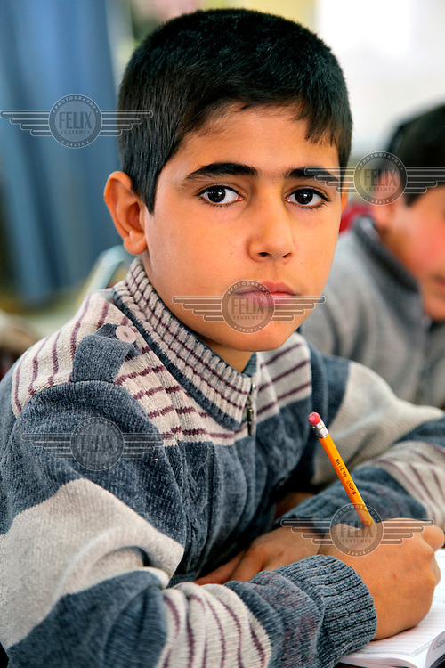 A Syrian refugee boy at an English class. UNICEF and partner organisation, the Jordanian Hashemite Fund for Human Development (JOHUD), run remedial education classes for vulnerable Syrian children. In addition to attending public schools, Syrian children require remedial education as there are differences between the two countries' curricula, and many children have been out of school since the outbreak of violence in March 2011. Remedial education will allow Syrian children to catch-up on curricula, and thereby decrease the likelihood of them dropping out of school. It is also an opportunity for teachers and counsellors to detect protection related issues and psychosocial problems that children may face.