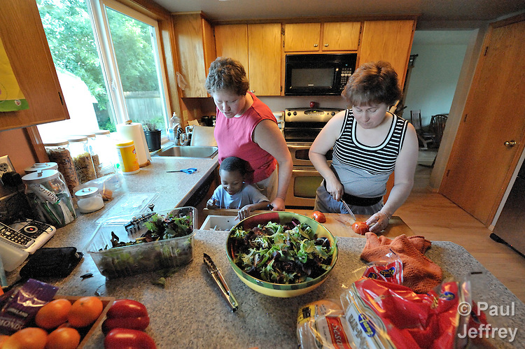 Barb (left) and Elaine Stellini, a lesbian couple in Vancouver, Washington, prepare dinner in their home. Sam, one of their three adopted boys, lends a hand.