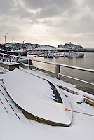 Snow covered row boat on dock at the Stamsund youth hostel, Samsund, Lofoten Islands, Norway