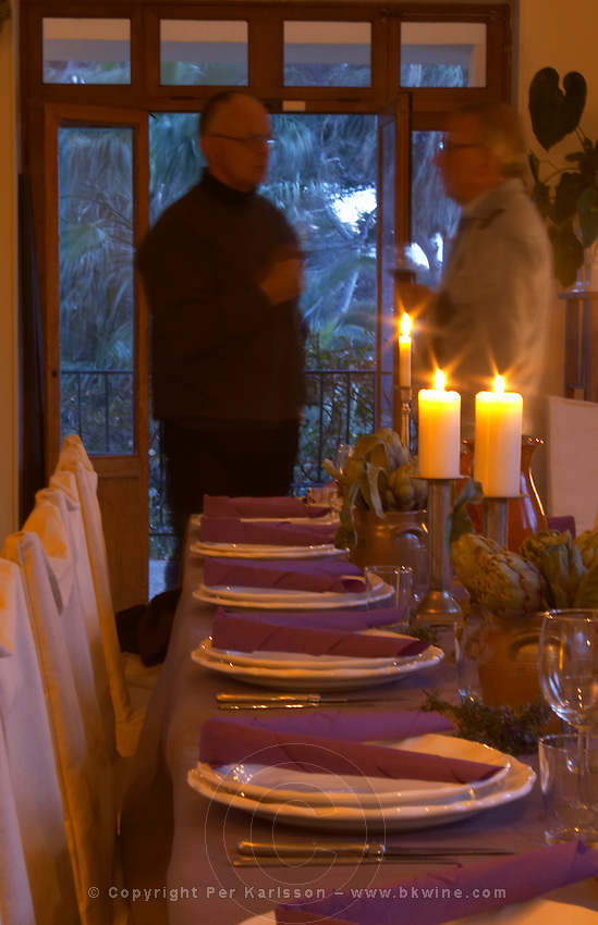 The dining room table decorated and set with flowers and decorative vegetables, candles, for dinner guests. Two men standing with aperitif glasses talking waiting for dinner Clos des Iles Le Brusc Six Fours Cote d'Azur Var France