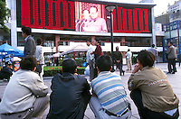 On Shanghai's Nanjing Road, pedestrians take a break and watch a re-run of Former President Jiang Zheming's National Day Speech. Despite stepping down from the post of the party secretary in November 2002, Jiang remains the real power in China with his control of the military..02-OCT-01