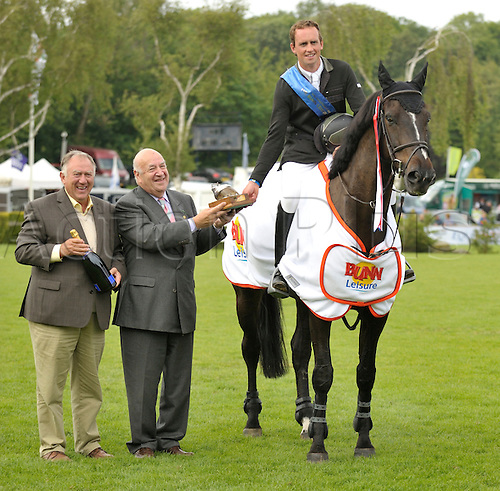 23.06.2012 The All England Jumping Course  Hickstead, England. David Broome CBE and Neil Benson present the Liz Dudden Memorial Trophy to Trevor Breen & Beer Hunter. The Bunn Leisure Speed Derby for the Liz Dudden Memorial Trophy at The British Jumping Derby Meeting.