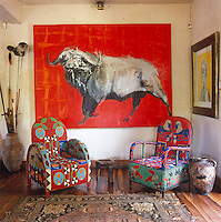 A pair of colourful beaded African chairs in front of a painting by Tonio Trzebinski