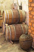 Old oak barrels and an old demijohn in a wicker basket in the wine cellar. Matusko Winery. Potmje village, Dingac wine region, Peljesac peninsula. Matusko Winery. Dingac village and region. Peljesac peninsula. Dalmatian Coast, Croatia, Europe.