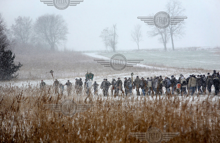 "Men walk through snow-covered fields during the Easter Procession in Dobra, Eastern Wielkopolska. For over 150 years this festival has taken place on Easter Monday. Known as Emmaus or ""meus"", as it's called locally, the festival is in memory of the Biblical story of the Apostles' journey to Emmaus. Similar festivities take place in other parts of the country, but they only walk around the Church, whilst in Dobra, all of the 15 roadside shrines located in the parish area are visited. It also differentiates itself from other Emmaus processions by the fact that only men participate.."