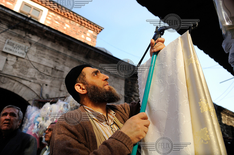 Bearded cloth seller at the Egyptian/Spice Market (Misir Carsisi), built in 1660s close to the Golden Horn in Eminonu.