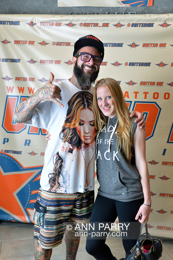 Garden City, New York, USA. September 13, 2015. Mark and a young woman pose at the Instagram photo booth at the United Ink Flight 915 Tattoo convention at the Cradle of Aviation Museum in Long Island.