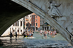 People on boards paddle down the Grand Canal and under the Rialto Bridge (Ponte Rialto) in Venice, Italy