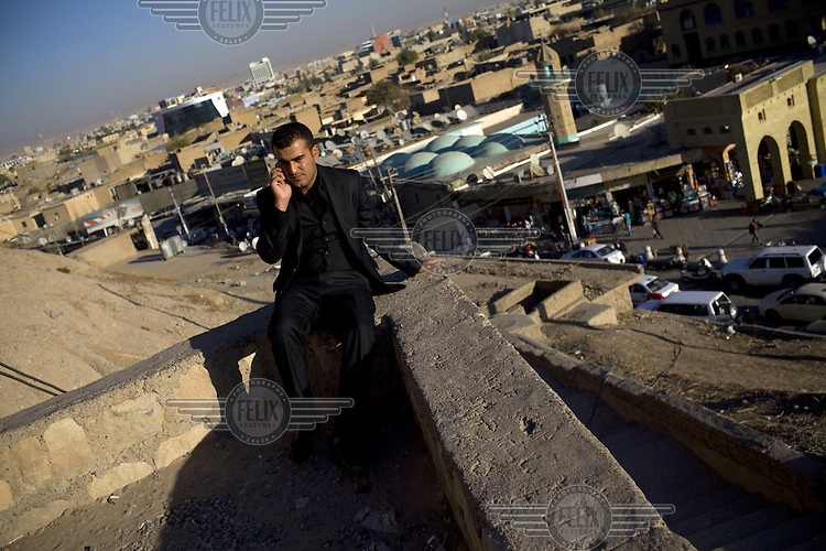 A man stands talking on his mobile phone by a wall overlooking Erbil in Iraqi Kurdistan.